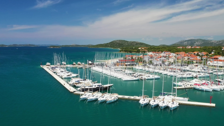 Yachts and boats in marina in town of Pirovac on Adriatic sea in Croatia, drone footage circle view