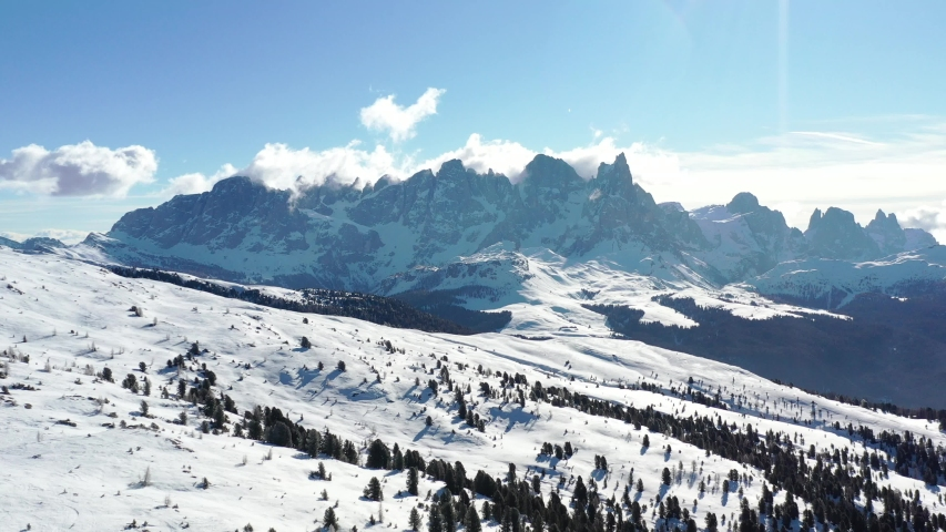 Drone footage aerial in winter snow ski sunny days - Ski Area Alpe Lusia, Moena region, Italian Dolomites. The camera slides down smoothly