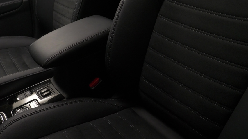 Panning from down to up of the interior of a luxury car with leather upholstery seats and door.