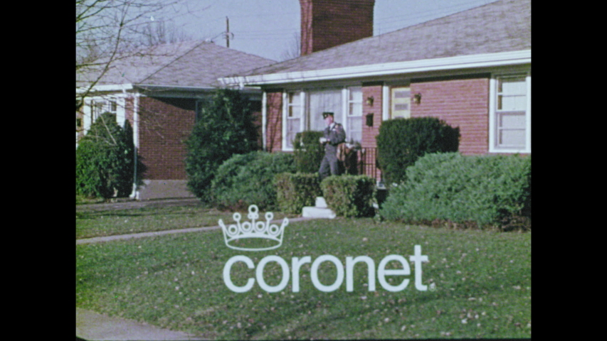 1970s: Boy rides bicycle across street, gets off bike, unties newspaper bundle. Mailman walks up to house, drops off mail.