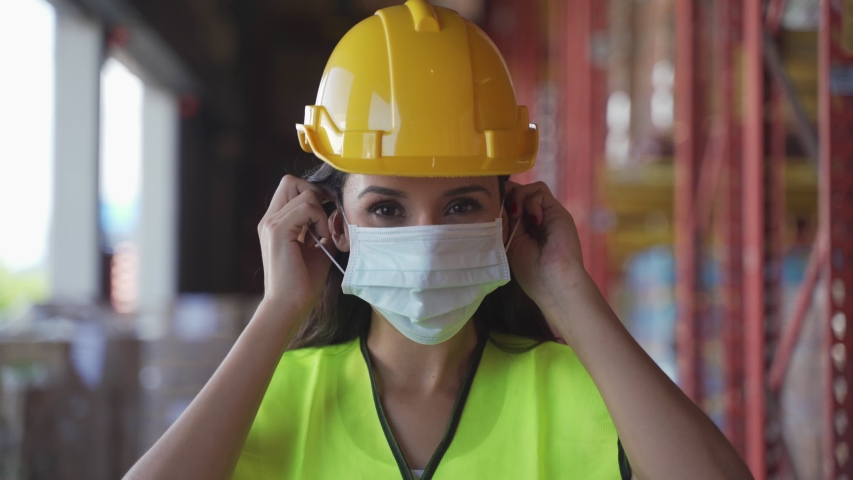 Portrait female worker with safety vest, hard helmet wearing face mask standing in warehouse factory due to covid pandemic crisis. Girl working in logistic and storage industrial with care of health.