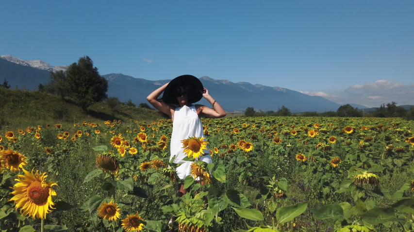 Happy young hispanic woman in a sunflower field