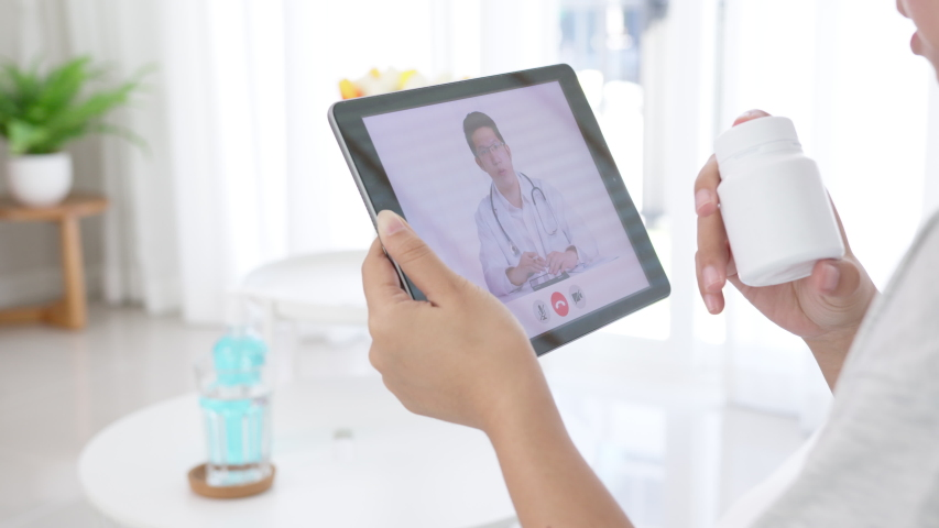 Telemedicine concept close up of asian woman video call with doctor at living room home. Patient girl consulting with general practitioner application computer tablet. Doctor and Consultant online
