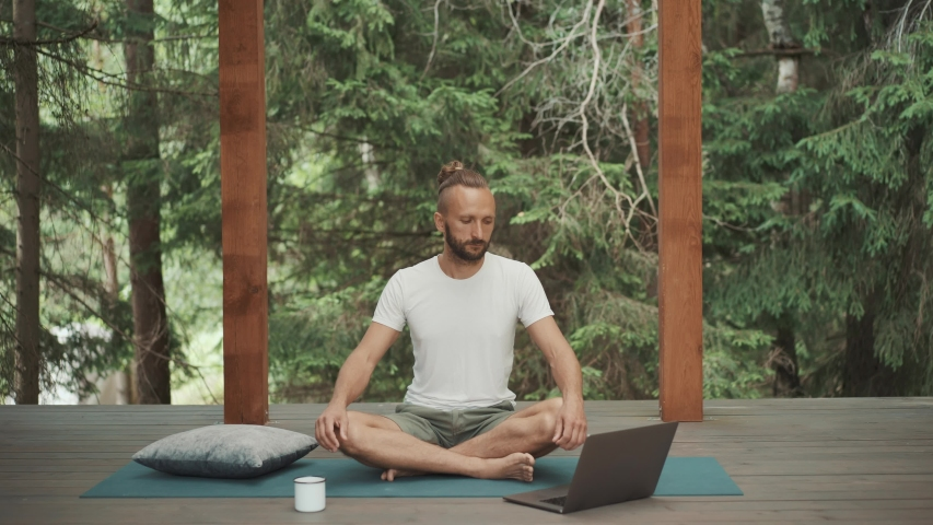 Handsome office man in white t-shirt try to meditate with online guiding on laptop. Beginner in yoga practice checks when timer ends. Difficult to sit long time. Terrace on green forest background    Shutterstock HD Video #1056136331