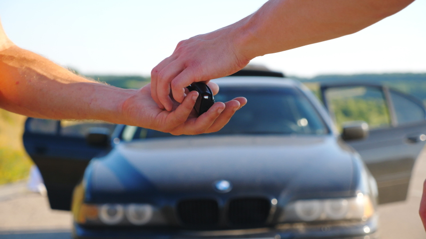 Unrecognizable man getting car key from seller. Male hands giving keys of car to his friend outdoor. Handshake between salesman and new owner of automobile after deal. Slow motion Close up