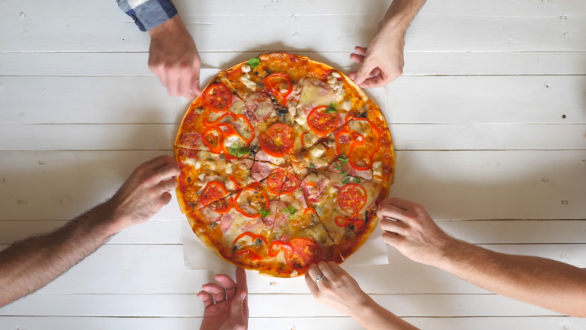 Top view male and female hands taking slices of pizza with cheese, tomatoes and ham from food delivery. Group of hungry friends sitting at desk and sharing delicious lunch on wooden table background