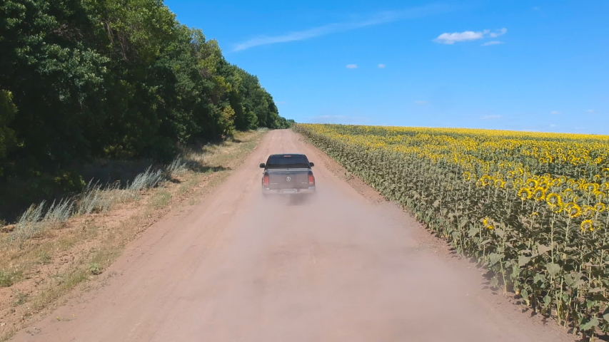 Aerial shot of black pickup truck fast riding through empty rural road. Off road vehicle going on dusty route near field. Flying over car driving at countryside way on summer day. Concept of farming | Shutterstock HD Video #1056139691