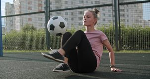 Young caucasian girl practicing soccer skills and tricks with the football ball at sunset in an playground. Urban city lifestyle outdoors concept. 4K UHD slow motion RAW graded footage