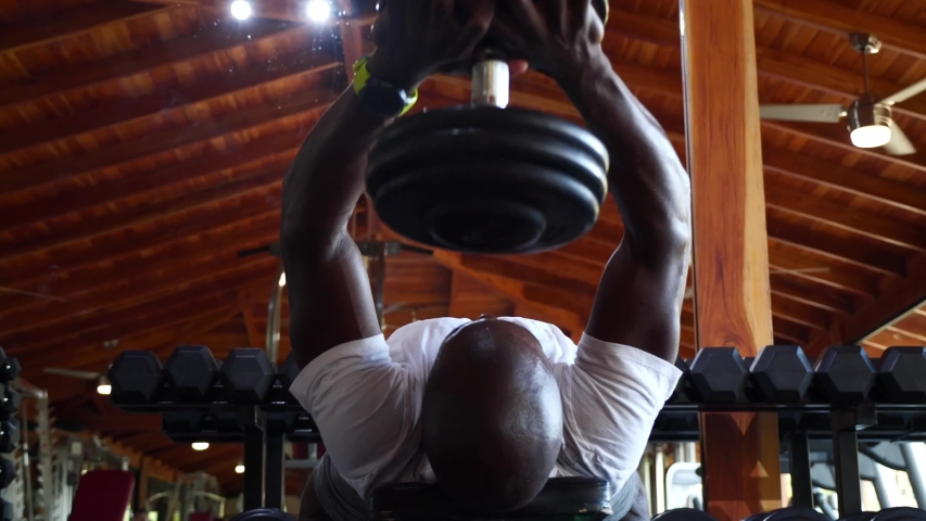 Black man bodybuilding weight lifting in a gym, fitness training. Slow motion. Concept of strength, endurance, vitality,  motivation, health goals.  Royalty-Free Stock Footage #1056140783