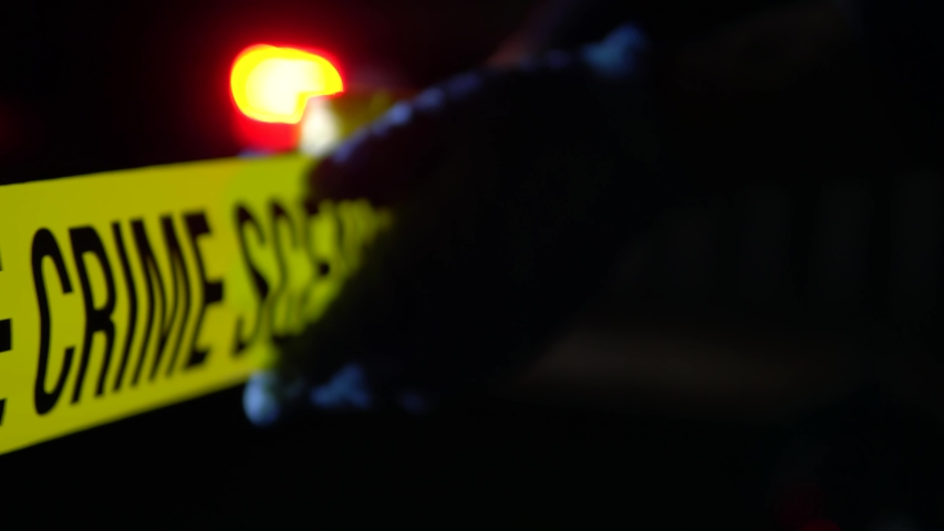 Police Officer Puts Up Barricade Crime Tape At Homicide Scene, At Night Outside