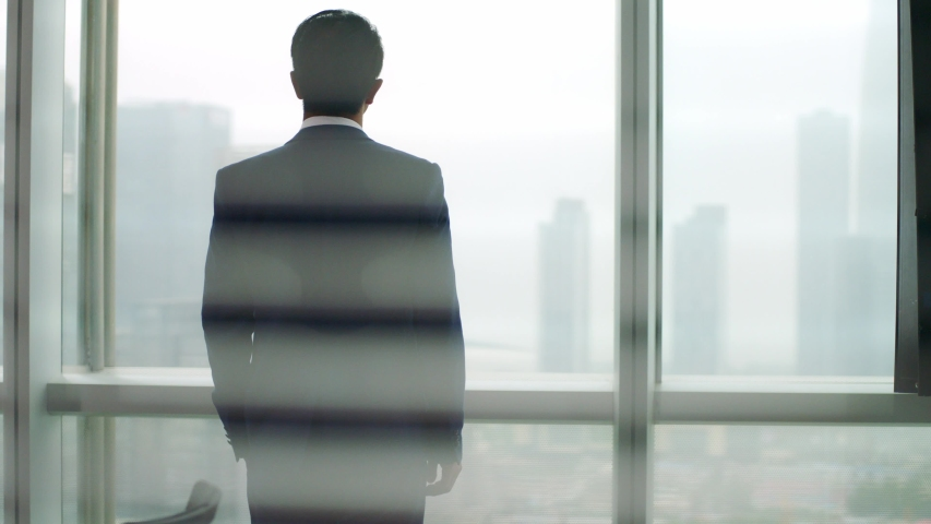 Rear view of a mature asian business man standing by the window in office looking out at modern buildings  | Shutterstock HD Video #1056144245