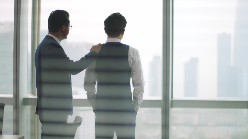 Mature asian manager comforting young business man standing in front of window | Shutterstock HD Video #1056144299