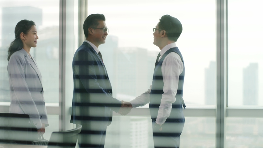 Young asian corporate executive welcoming and shaking hands with visiting client in front of windows in office
