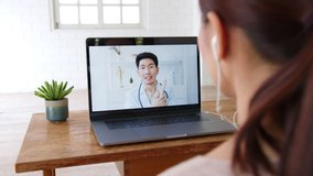 Asian woman talking with doctor via computer laptop virtual video call or video conference at home, telehealth and telemedicine concept