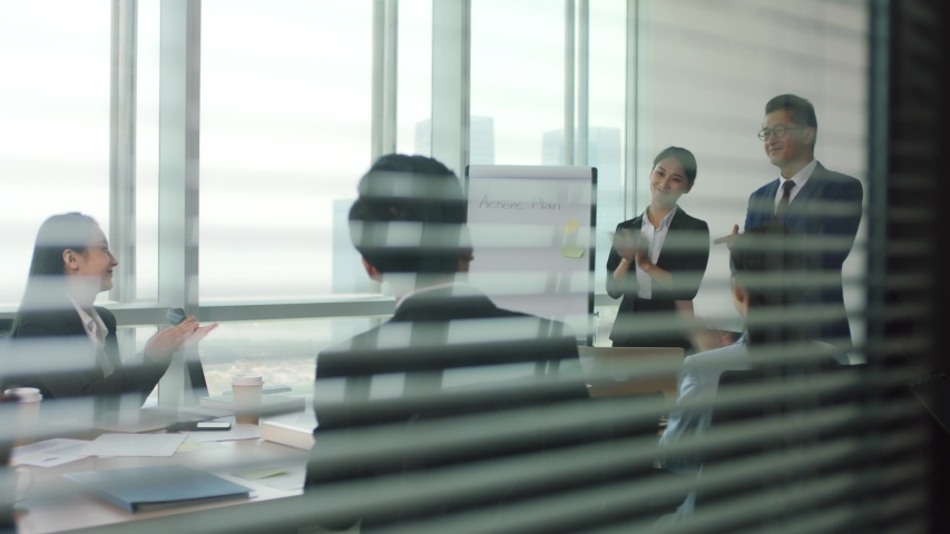 Asian manager introducing new team member during staff meeting in modern office conference room | Shutterstock HD Video #1056146558