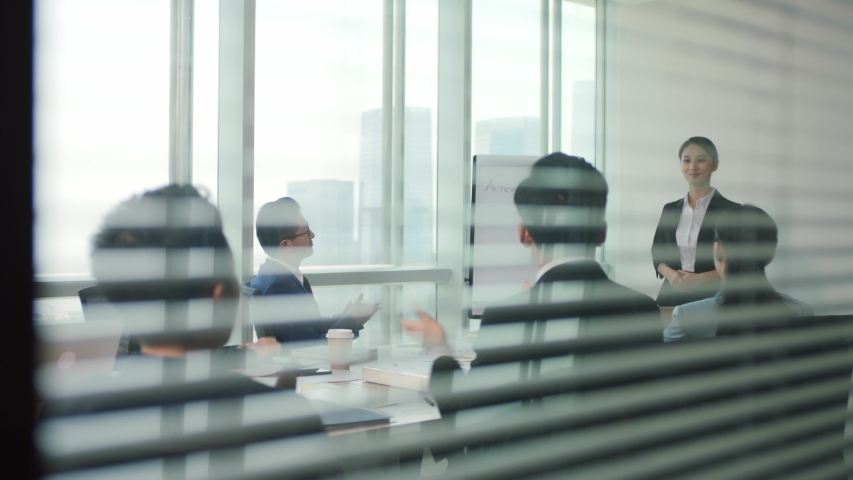 Junior asian executive presenting business plan to team during staff meeting in modern office conference room | Shutterstock HD Video #1056146798