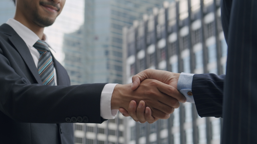 Close up. Hand of two Asian business people gathered to handshake agree to a deal or say hello On the background of building in city