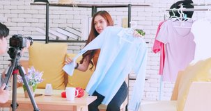 Young Asia couple selling fashion clothes online by live streaming with digital camera.