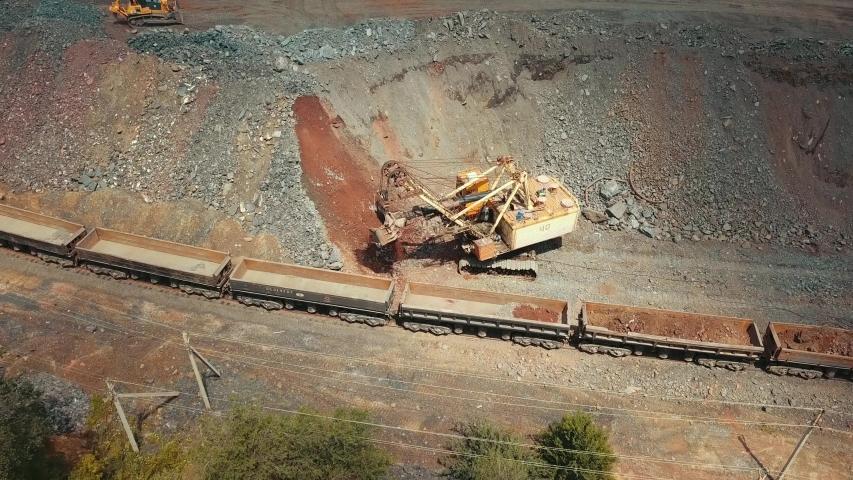 Excavator quarry loading train iron ore industry mining.
