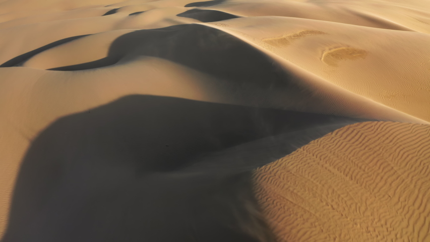 Incredible aerial shot of strong wind blowing away the golden sand from the tops of high dunes in sunset light. Cinematic background with ripples texture on the surface of desert nature
