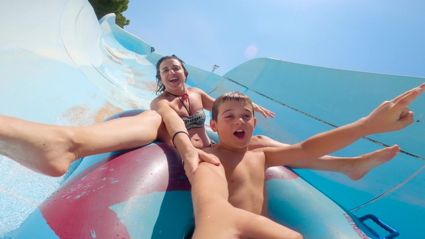 Selfie of son and mother having fun, going down a water slide on a rubber ring. Sliding at a Water Amusement Park on summer vacation. Royalty-Free Stock Footage #1056152663