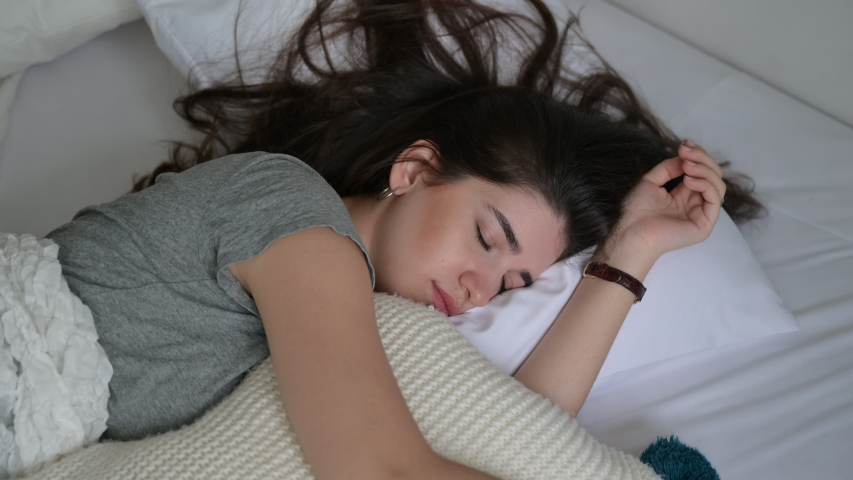 Calm young woman sleeping well in comfortable cozy white bed with soft pillow, peaceful serene girl resting lying asleep enjoying healthy good sleep nap in the morning at home   Shutterstock HD Video #1056152879