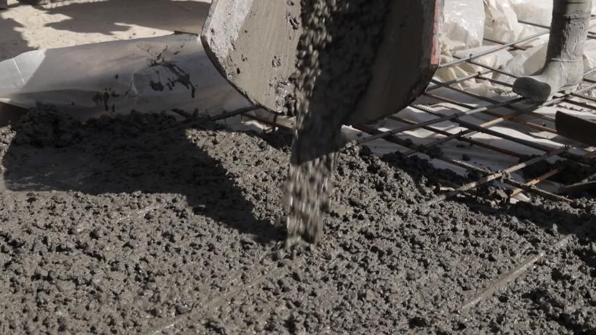 The concrete mix is fed from a concrete mixer. Concreting. Concrete floor.