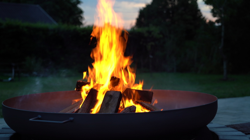 Iron fire pit and burning fire in a garden.