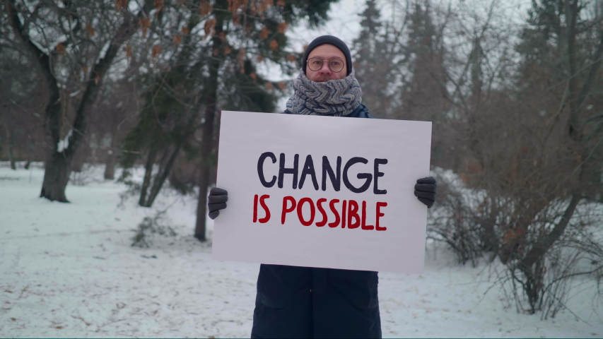 """""""Change is possible"""" sign, one man protest, caucasian male activist in a park picket at winter day calls for a change in the political regime in the country Royalty-Free Stock Footage #1056164117"""