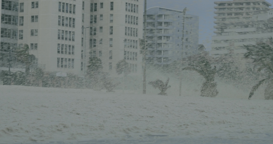 A white car drives on the foamy streets of Cape Town. Gale force winds cover the streets and air, with foam blown from the sea. Palm trees are tossed uncontrollably in the winds. Beige residential apa