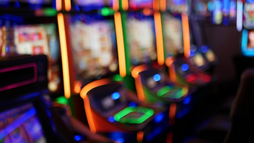 Defocused slot machines glow in casino on fabulous Las Vegas Strip, USA. Blurred gambling jackpot slots in hotel near Fremont street. Illuminated neon fruit machine for risk money playing and betting. | Shutterstock HD Video #1056169619