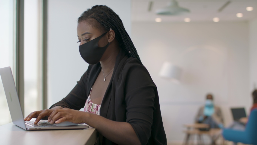 Back at work with social distance precautions. A black woman at a tech firm works on her laptop. Business is back. Shot in slow-motion and in 4k.  Royalty-Free Stock Footage #1056170840