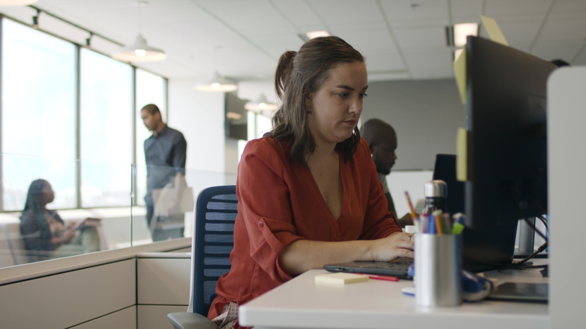 Coding at a technology company. A young woman programmer is hard at work at a tech company creating the next big app. Shot in slow-motion and in 4k.  Royalty-Free Stock Footage #1056171116