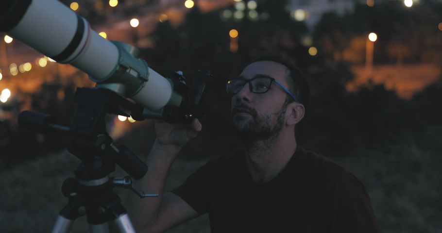 Astronomer with a telescope watching at the night sky with blurred city lights in the background. Royalty-Free Stock Footage #1056171146