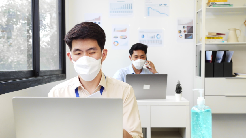 Asian business people wear face mask working in office to protect infection of coronavirus covid-19, reopen business with new normal and social distancing concept Royalty-Free Stock Footage #1056171281