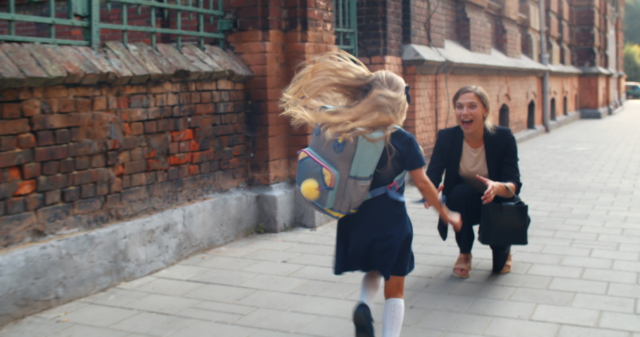 Happy small girl running to her smiling mother and jumping into her embrace after school.Chherful young woman picking up her little daughter and having fun with her at street | Shutterstock HD Video #1056174830