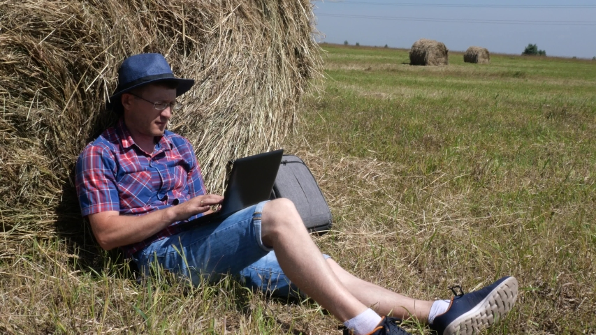 A man with a laptop sits by a haystack.