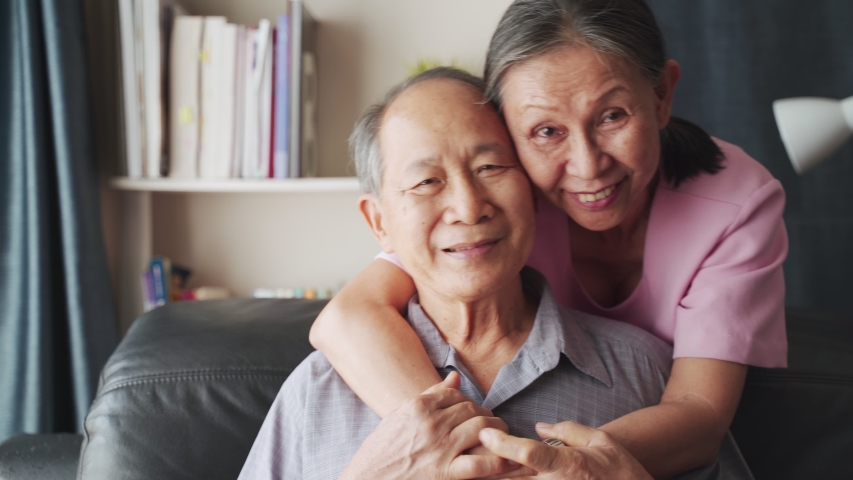 Portrait of Asian mature couple sitting and smiling in living room. Old woman hug man from behind and look at camera with happiness. Happy life after retirement, grandparents enjoy activity together. Royalty-Free Stock Footage #1056176609