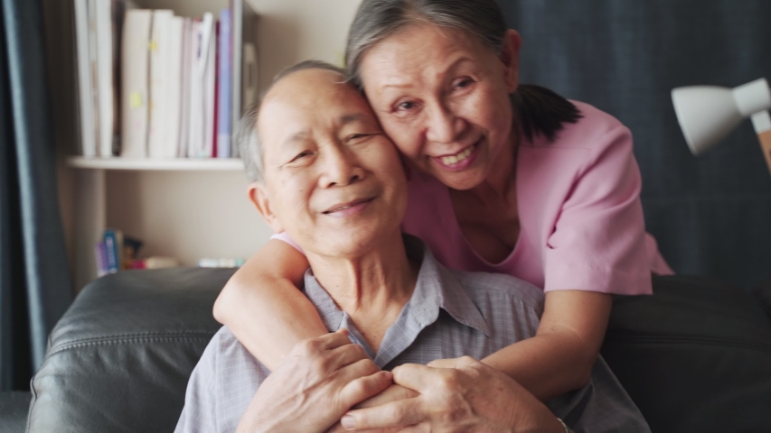 Portrait of Asian mature couple sitting and smiling in living room. Old woman hug man from behind and look at camera with happiness. Happy life after retirement, grandparents enjoy activity together.