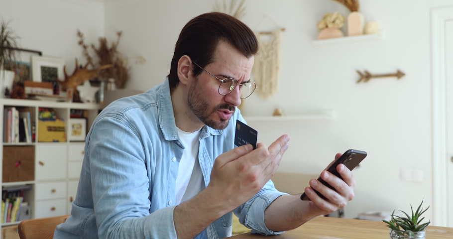 Millennial man in glasses sit at table hold smartphone and credit card frowns try to make payment through internet feels angry due lack of money, insufficient not enough funds. Victim of fraud concept Royalty-Free Stock Footage #1056178973
