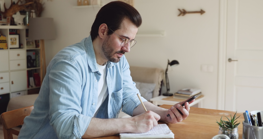 Millennial guy in glasses sit at desk in domestic room hold pencil writing creative ideas on notebook, plan memo list to do use internet or agenda on smartphone. Studying or working activity concept Royalty-Free Stock Footage #1056178979