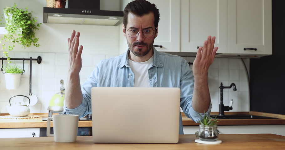 Man sit at table in kitchen feels annoyed having problems with laptop. System error, bad e-mail, negative news, data loss, backup battery issues, password wrong, unsaved, lost info need repair concept