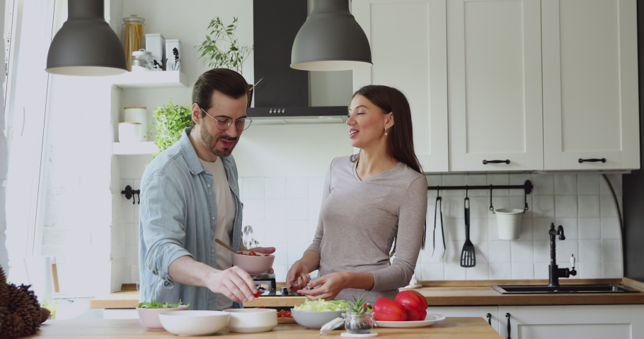 Loving couple feed each other while cooking together in modern kitchen enjoy conversation and healthy vegetarian salad food preparation. Lifestyle, happy homeowners, romantic date, hobby, love concept