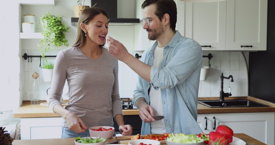 Young married couple talking while preparing vegetable salad on domestic modern kitchen. Healthy lifestyle, routine activity together, harmonic relationships common hobby, vegetarian family concept #1056179036