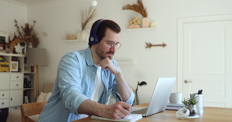 Millennial man sit at desk in living room looks at laptop screen listen audio through headphones use exercise book makes notes learn language develop improve gain new knowledge. Self-education concept