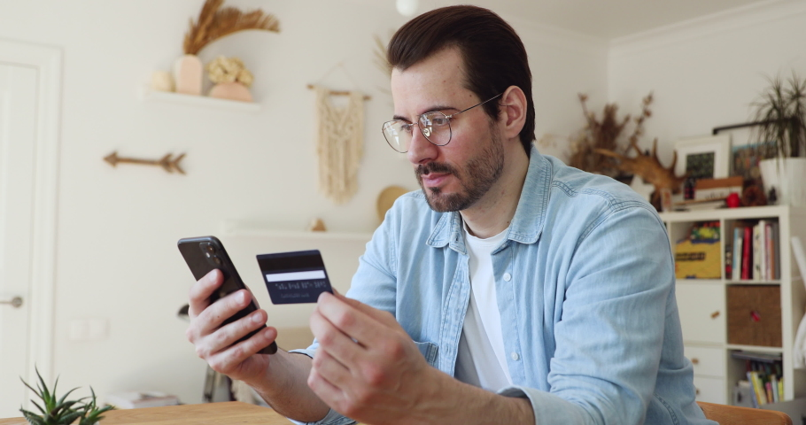 Serious handsome young man in glasses sit at home domestic room holds credit card use cellphone app make payment buy goods or services on internet. E-commerce, secure easy quick money transfer concept Royalty-Free Stock Footage #1056179264