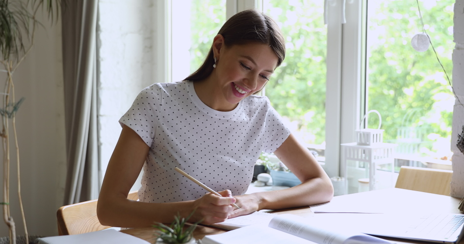 Young woman sitting at desk writing summary, creative essay, enjoy interesting learning process, make topic research, develop thesis, gain new knowledge, busy exam preparation, self-education concept Royalty-Free Stock Footage #1056179300