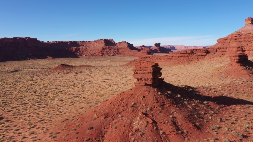 Red rocks butte of brick canyon formation crumbling from erosion. High cliffs of famous grand canyon of red sand sandstone in dried sunny desert of western usa. Aerial view, drone flies right