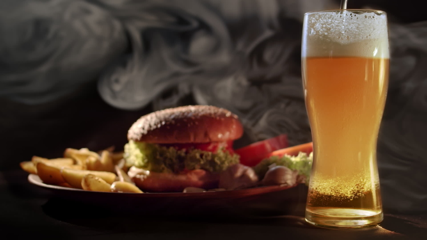 Burger with baked potatoes and beer | Shutterstock HD Video #1056187811