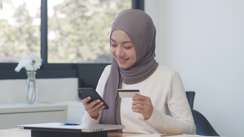 Asia muslim lady using phone, credit card buy and purchase e-commerce internet in office. Stay at home, online shopping, self isolation, social distancing, quarantine for coronavirus prevention. Royalty-Free Stock Footage #1056187820